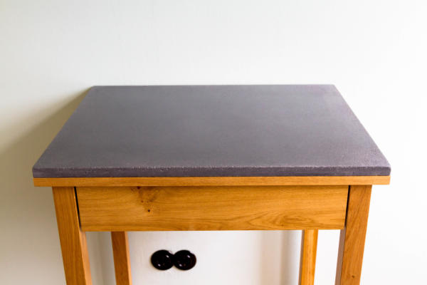 keukentafel met lade van massief eiken gelakt met blanke lak met zwart betonnen blad