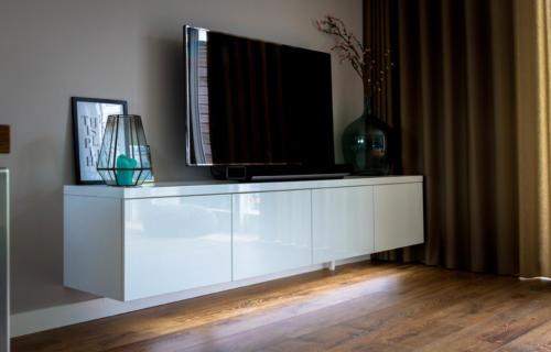 Tv kast met hoogglans spuitwerk onder de kast zit een strip ledverlichting en push to open deurtjes