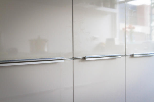 moderne hoogglans keukenkasten met chromen greeplijsten