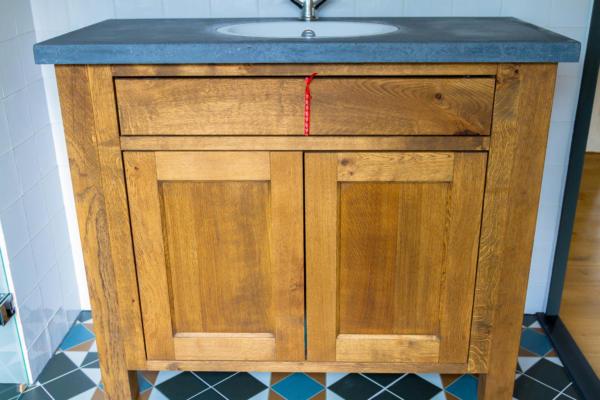massief eiken badkamer meubel gebeitst landelijke uitstraling met zwart betonnen werkplat en keramiek spoelbak